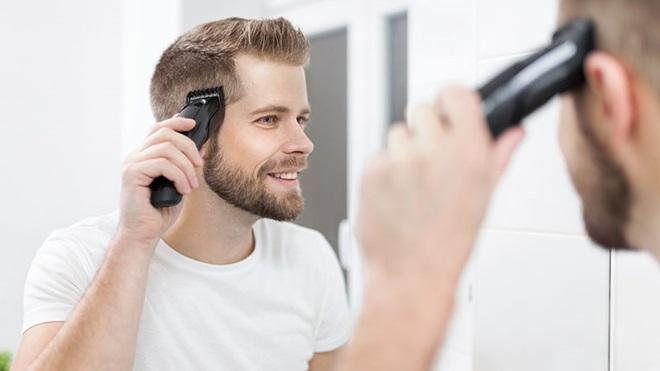 homem a cortar o cabelo com máquina