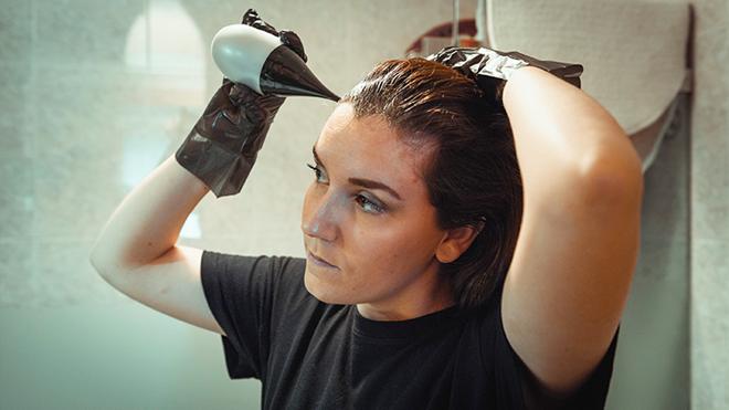 Mulher a aplicar tinta no cabelo em casa