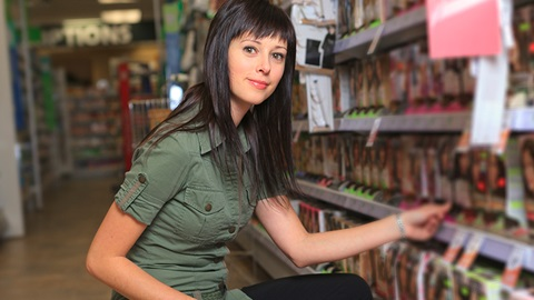 rapariga de vestido verde-escuro e cabelo comprido preto a retirar embalagem de tinta para cabelo da prateleira do supermercado