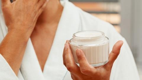 mulher de roupão branco a aplicar um creme de rosto