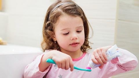 Menina de pijama cor de rosa a pôr dentífrico numa escova azul para lavar os dentes.
