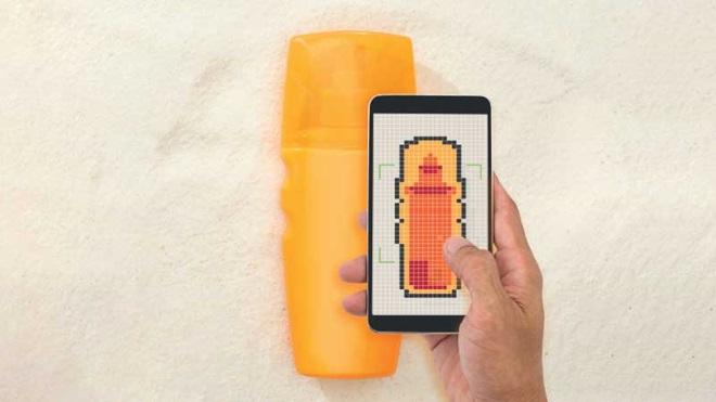 Mão segura telemóvel apontado a uma embalagem amarela de protetor solar, para verificação do conteúdo, como se fosse um scanner