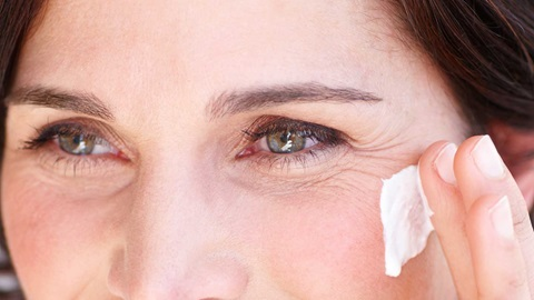 Imagem de detalhe dos olhos de uma senhora de meia idade e das suas rugas de expressão, enquanto aplica com a ponta dos dedos um creme de rosto.