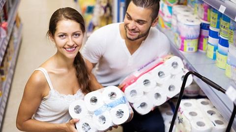 Um casal sorridente e jovem encontra-se num supermercado, junto a uma prateleira de produtos de higiene. A mulher do casal segura uma embalagem de 12 rolos de papel higiénico e olha para a câmara. O homem do casal segura uma embalagem de 18 rolos de papel higiénico e olha para a mulher.