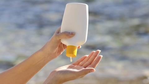 mãos a colocar protetor solar na praia
