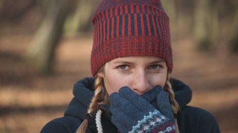 mulher com gorro e luvas a proteger cara do frio