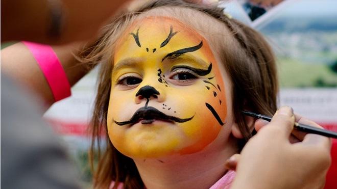 Criança a fazer pinturas de carnaval na cara