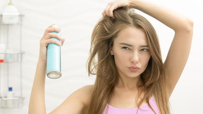 rapariga a pulverizar champô seco no cabelo