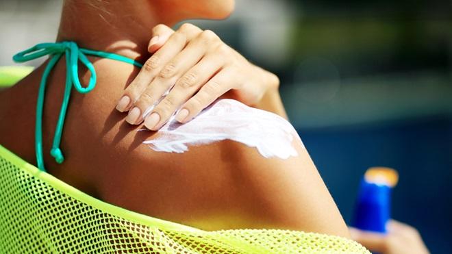 Mulher a pôr protetor solar nas costas