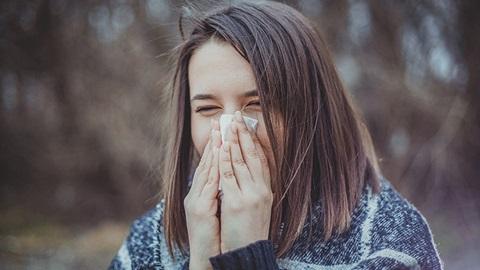 rapariga com alergia a assoar o nariz a um lenço de papel