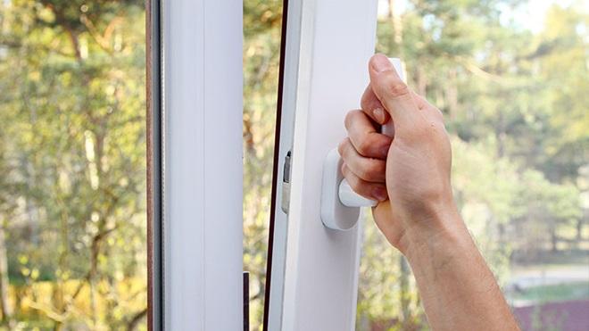 pessoa a abrir janela para arejar a casa
