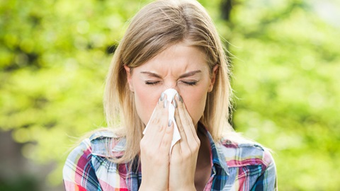 mulher constipada a assoar nariz