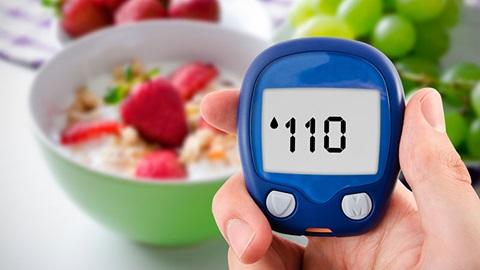 medidor de níveis de diabetes numa mão com taça de cereais e fruta ao fundo