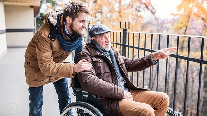 rapaz a empurrar homem numa cadeira de rodas