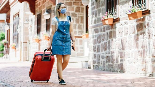 Desconfinamento: turista de máscara a andar na rua com mala de viagem