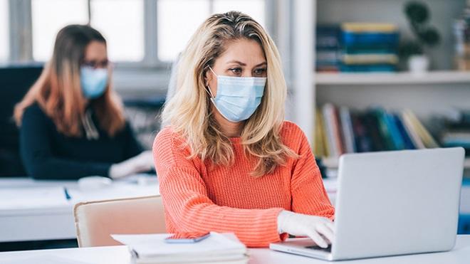 mulheres a trabalhar em escritório com máscaras