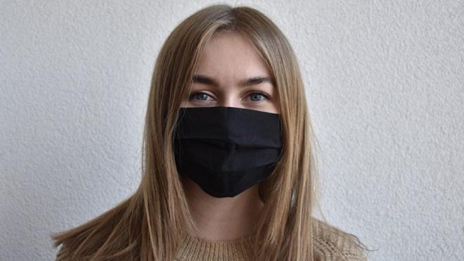 mulher com máscara social reutilizável preta