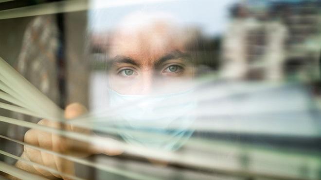 pessoa em isolamento ou quarentena por covid-19 olha através de uma persiana de uma janela