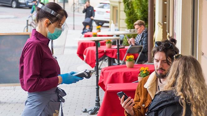 pessoas na esplanada de restaurante a serem atendidas por funcionária com viseira e máscara