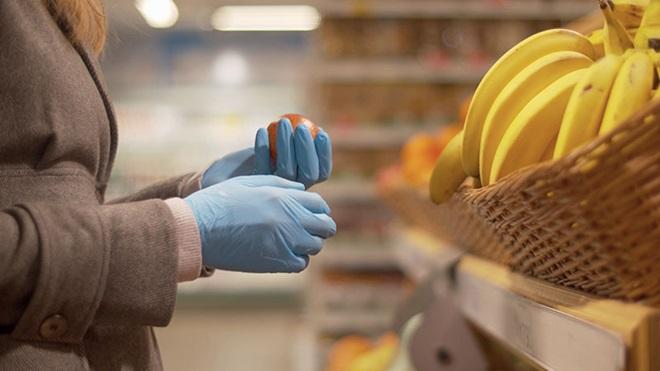 mulher a comprar maçãs e bananas com luvas azuis