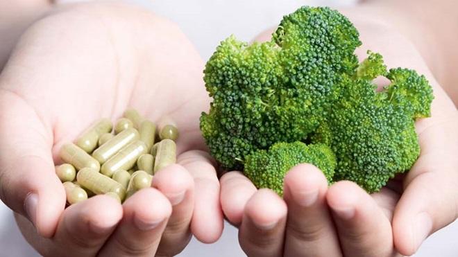 Uma mão com suplementos alimentares e outra com um bróculo