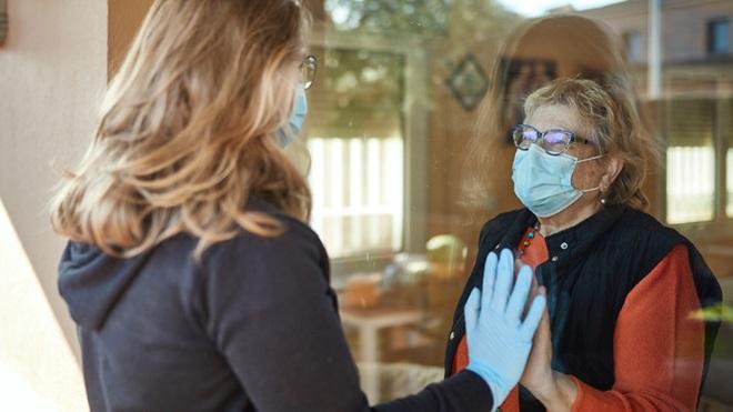 rapariga a visitar familiar com máscaras e através de um vidro