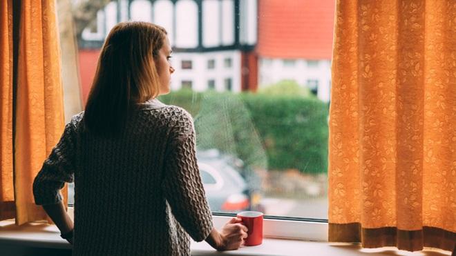 mulher em casa a olhar pela janela com uma caneca de chá na mão