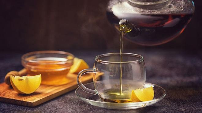 Chávena de chá de limão com tigela de mel ao lado