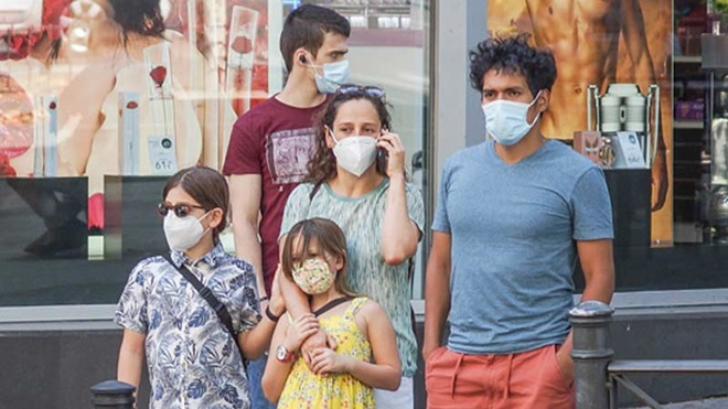Família de cinco pessoas de diferentes idades a usar máscara comunitária