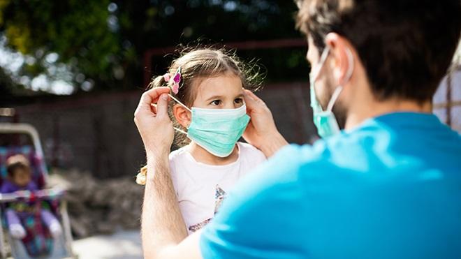 pai coloca máscara cirúrgica descartável em criança