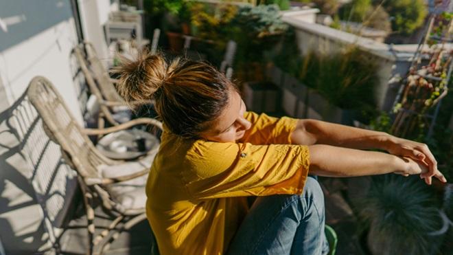 mulher de mangas arregaçadas a apanhar sol na cara e nos braços