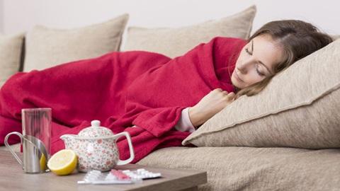 mulher deitada no sofá com constipação