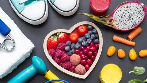 coração preenchido com vários frutos vermelhos, alguns objetos de ginástica, ténis, cenoura baby e outros alimentos saudáveis