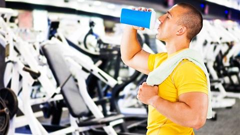 homem no ginásio a beber suplemento alimentar