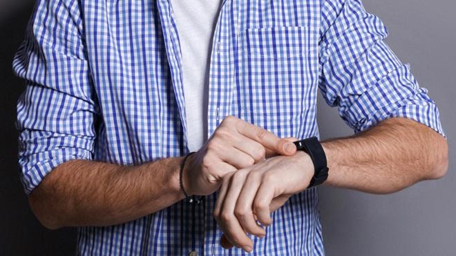 Mão de homem mexe no relógio inteligente, preso no pulso