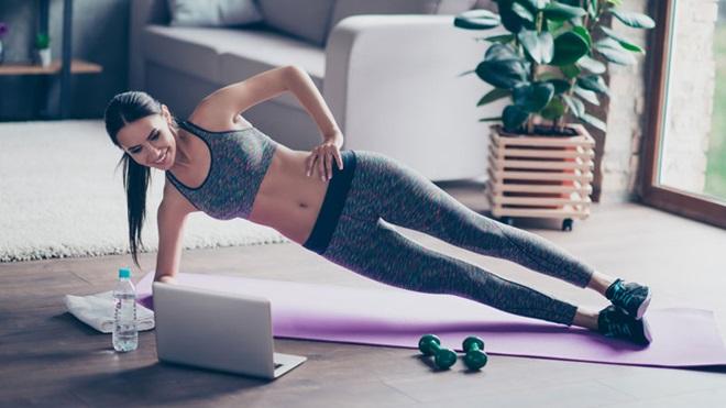 Mulher jovem a fazem exercício físico em casa, em frente a um computador