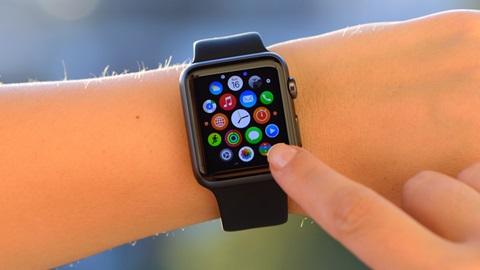 Imagem de um antebraço e mão, cujo pulso enverga um smartwatch. Ao centro, a mão direita manipula o smartwatch.