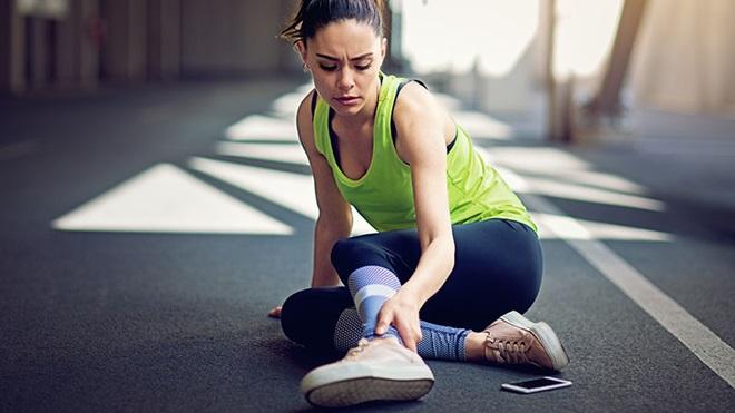 mulher atleta no chão a queixar-se de lesão no tornozelo