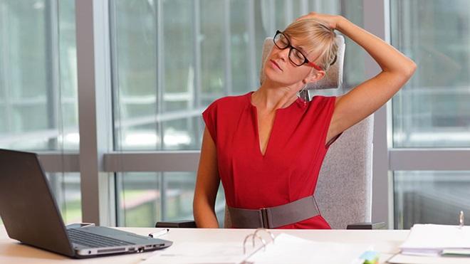 Mulher sentada ao computador a fazer exercício físico no escritório.