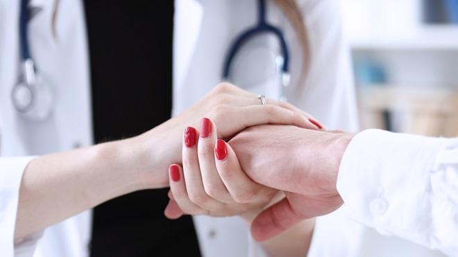 Médico a segurar a mão do paciente
