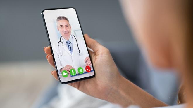 Mão feminina a segurar um telemóvel com a imagem de um médico
