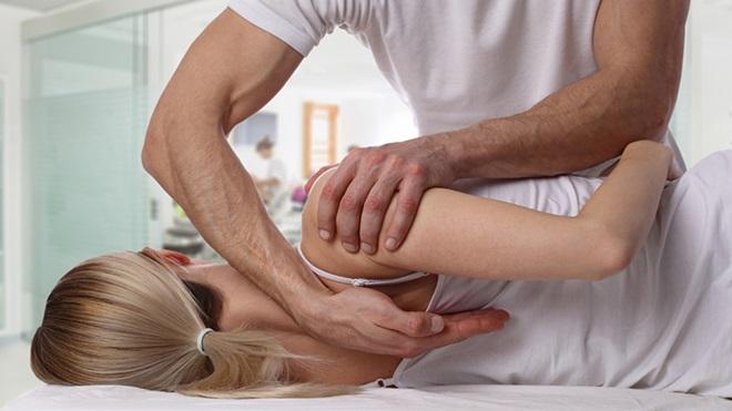 Terapeuta a endireitar as costas a uma paciente