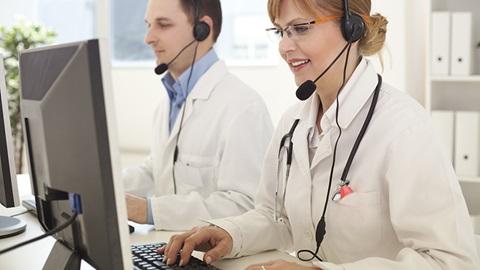 médicos a atender chamadas em frente ao computador