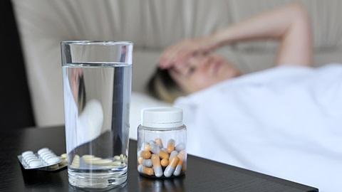 mulher deitada doente com copo de água e comprimidos na mesa