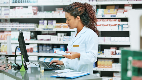 mulher em farmácia no computador