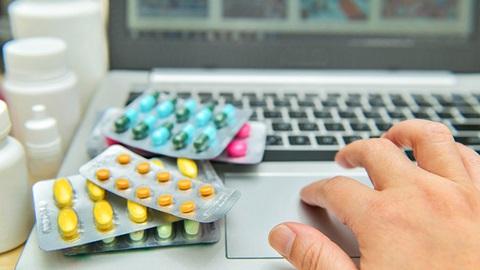 mão de utilizador ao computador a pesquisar medicamentos