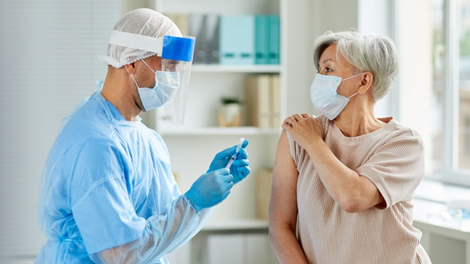 Enfermeiro a dar vacina de mARN contra a covid-19 a uma mulher.