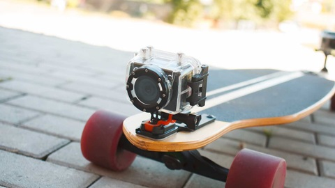 Sobre um pavimento de tijolos cinzentos, um skate com rodas vermelhas e prancha de madeira, com as cores preta e amarela. Por cima, uma câmara de vídeo aventura.