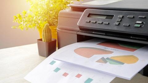 Pormenor de impressora a imprimir folhas com gráficos coloridos