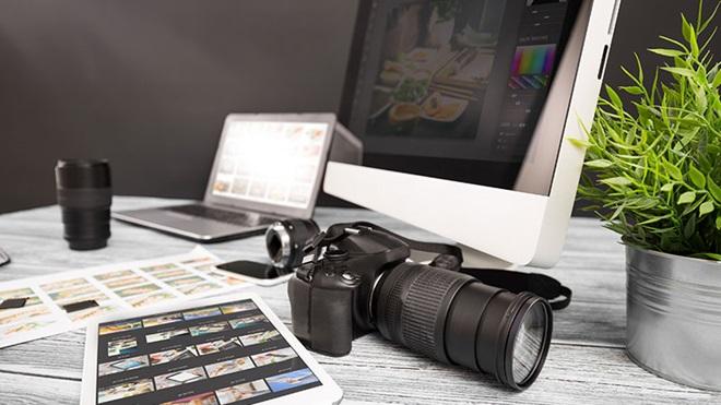 Máquina fotográfica, computador portátil, tablet com thumbnails, objetivas e provas de contacto sobre uma mesa de trabalho